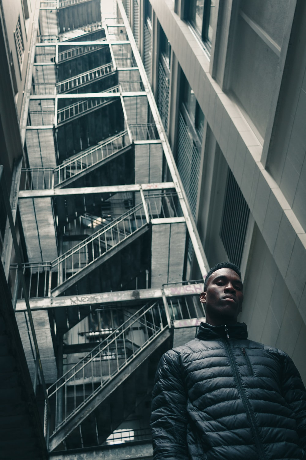 worm's eye view photography of man standing in front of white building