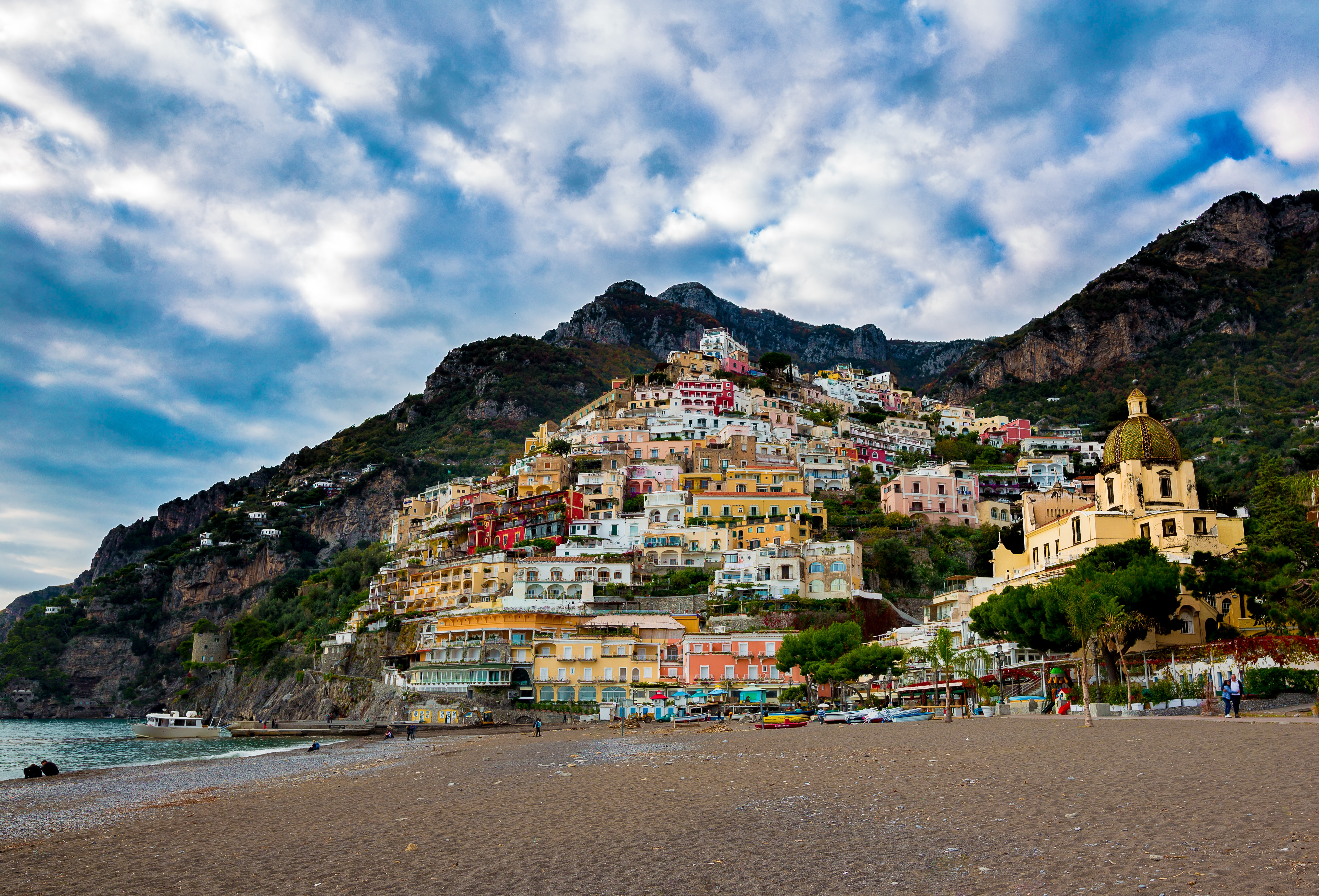 multicolored village on mountain under white and blue skies