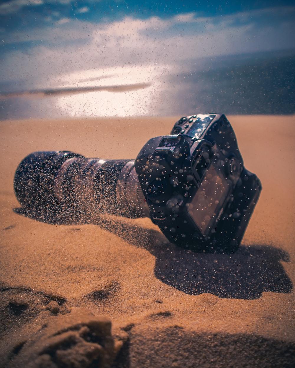 black DSLR camera on sand