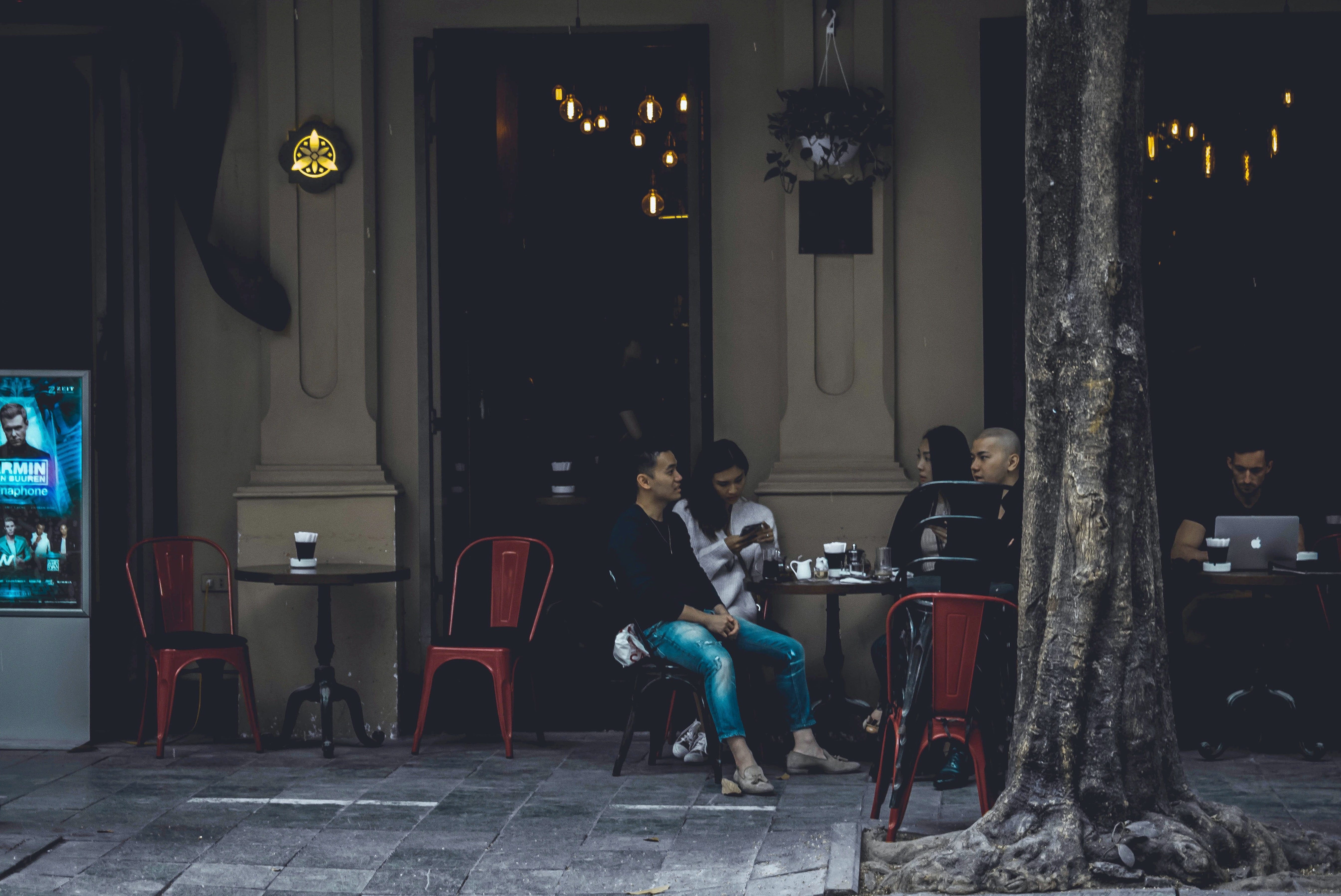 group of people sitting on chair with table in front of building