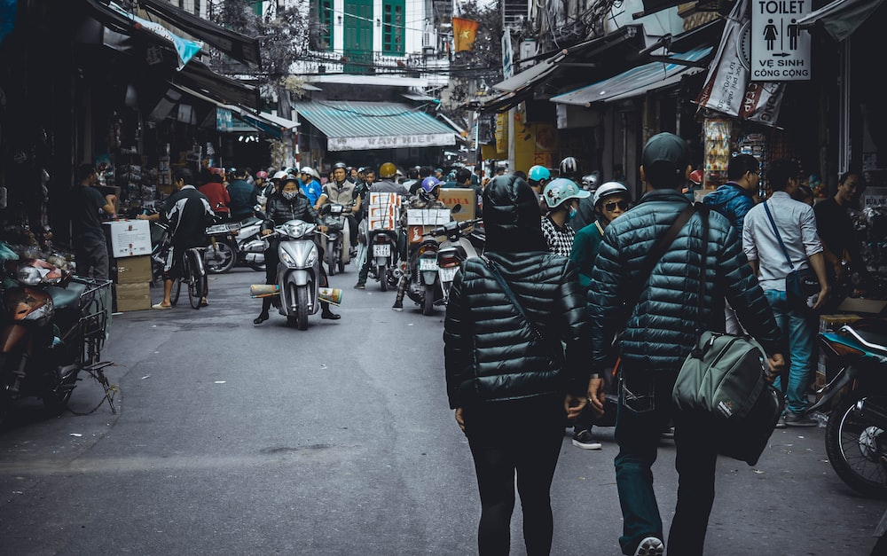 people walking on the street surrounded by concrete structures