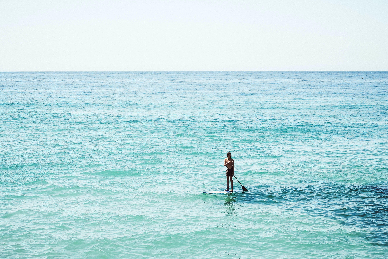 man on surfboard under white sky