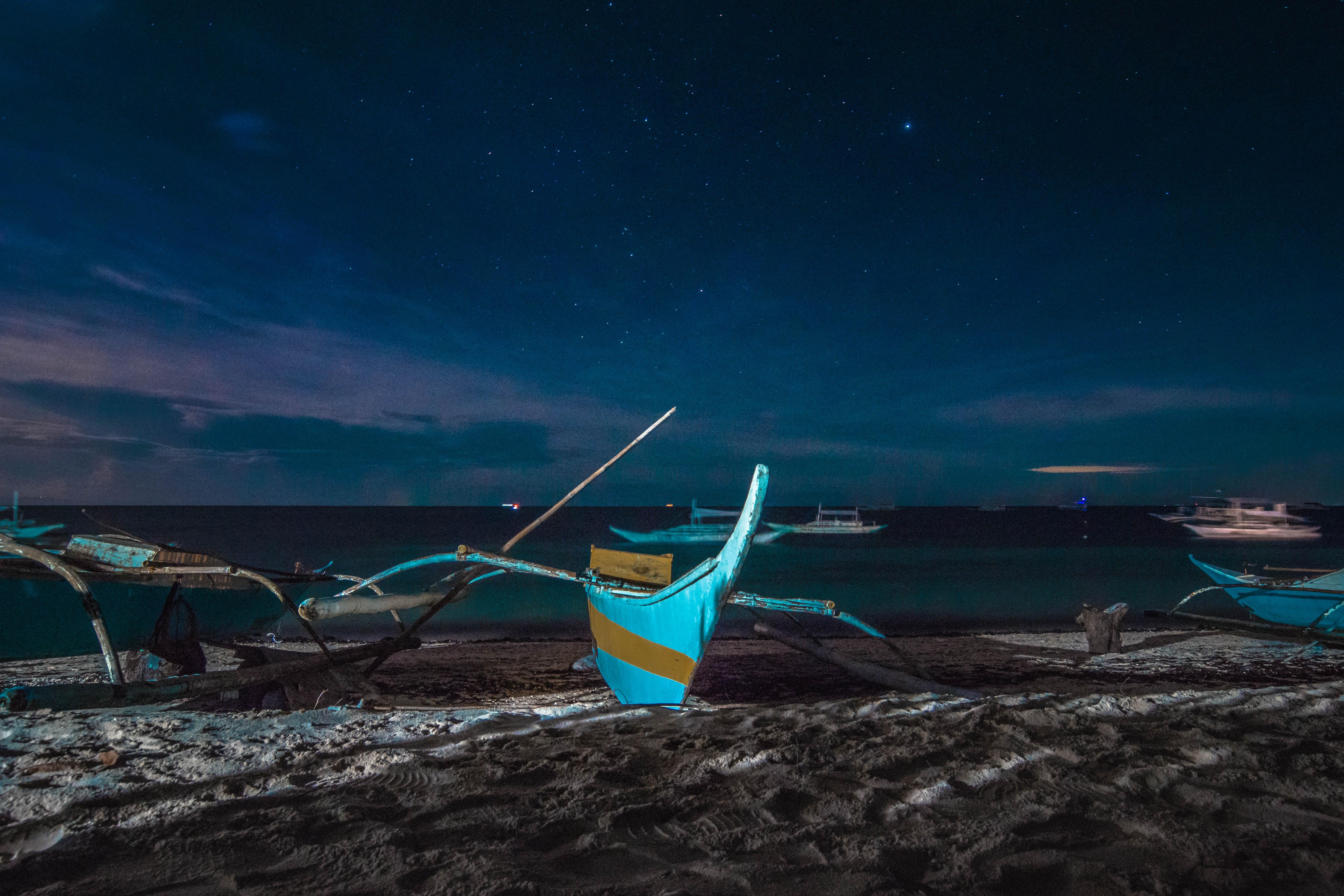 canoe boats near seashore during night