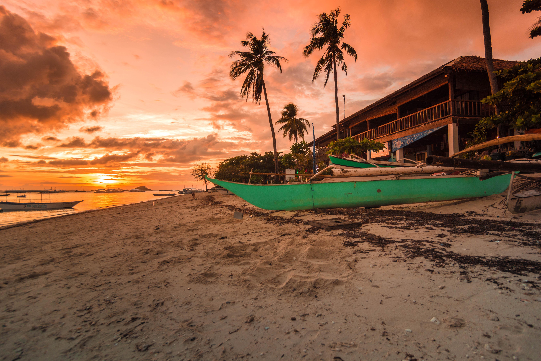 boat on seashore during sunset