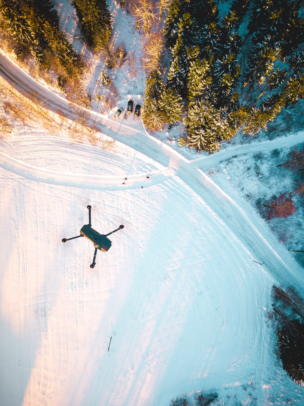 black quadcopter drone flying over snow field during daytime