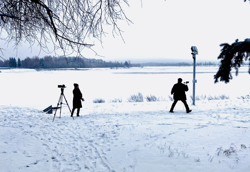man filming on snow field