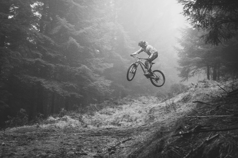 grayscale photography of person riding bicycle in forest