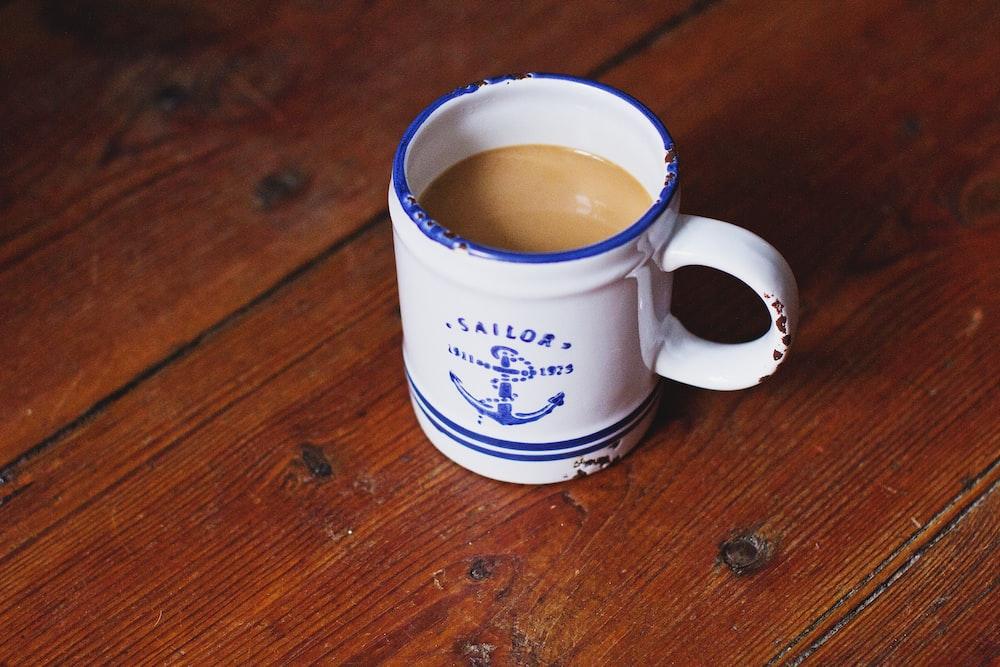 ceramic mug filled with brown liquid
