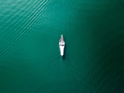 aerial photography of white boat on the middle of calm water