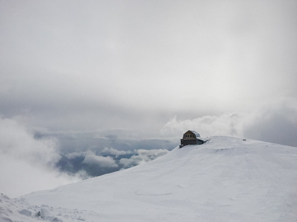 snow covered house under white clouds