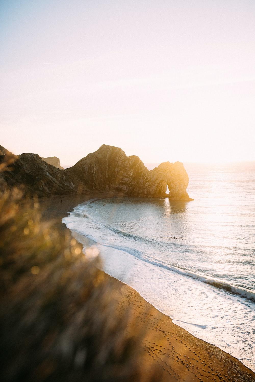 rock monolith beside calm body of water