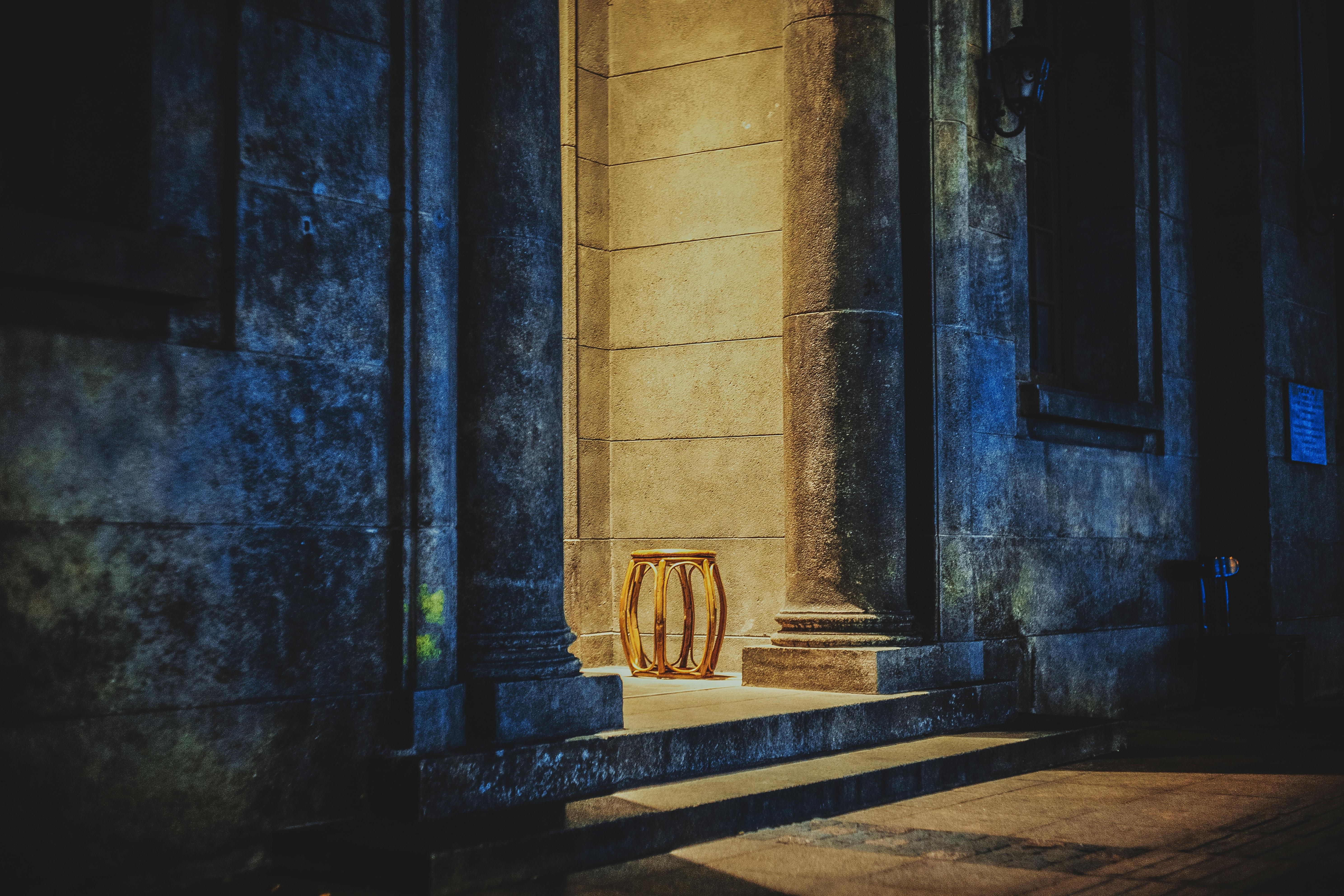 brown wooden stool beside concrete pillar