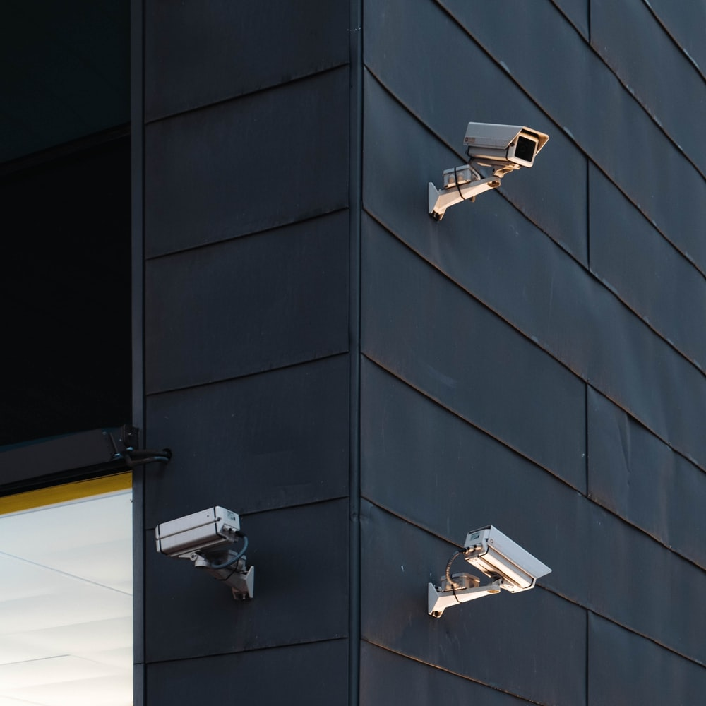 three white CCTV camera on building wall
