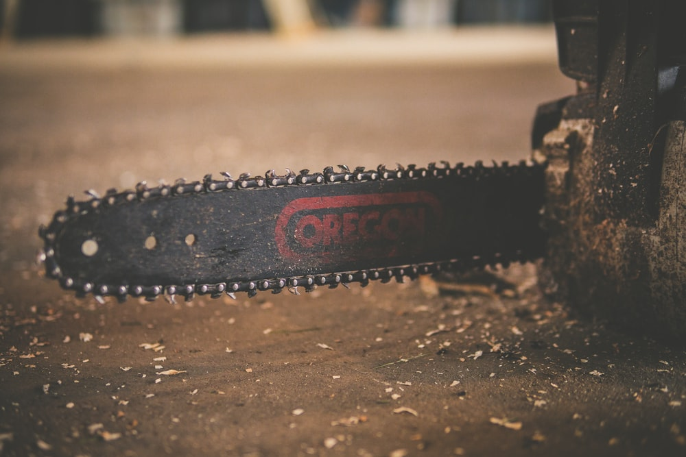 black and red Oregon chainsaw on brown wood plank