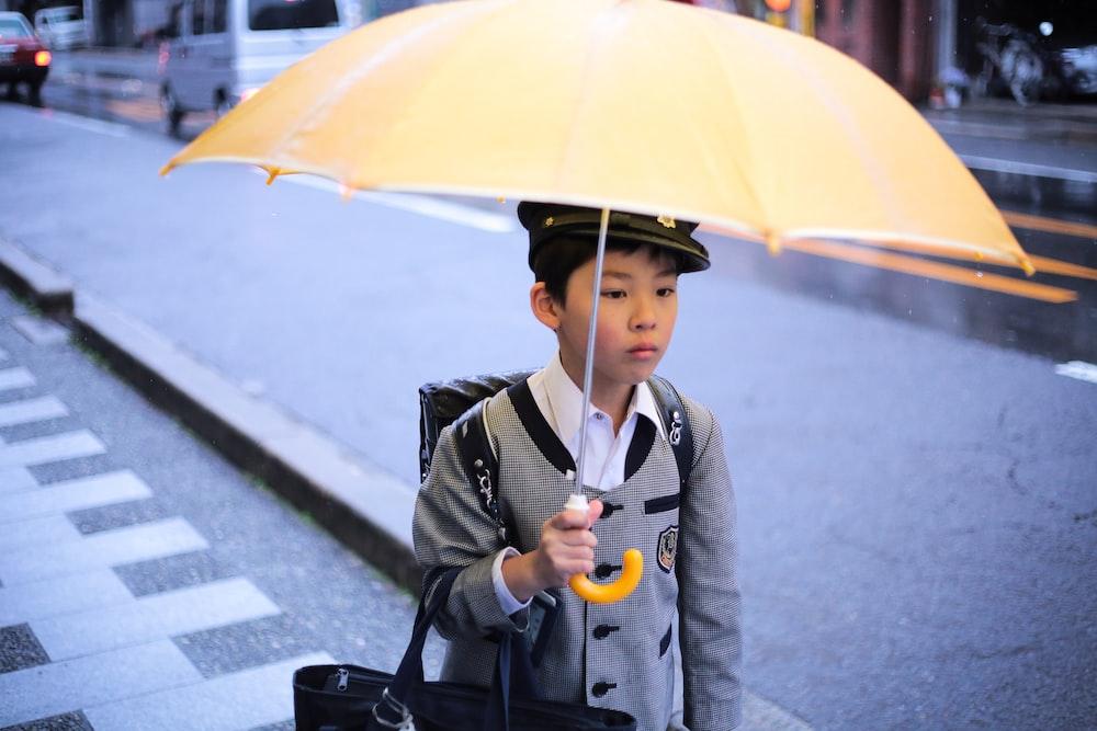 boy holding yellow umbrella