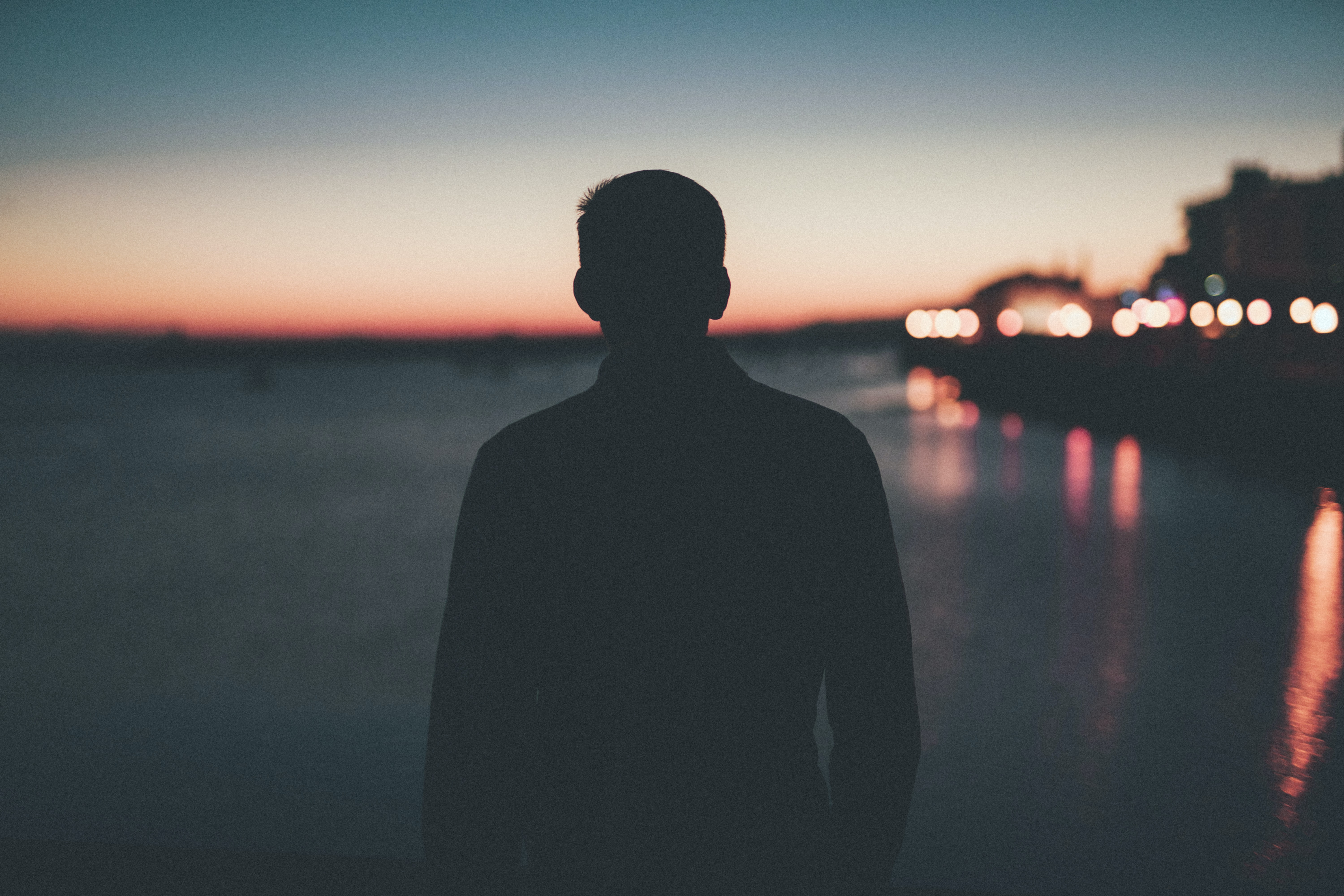 silhouette of man front of sea