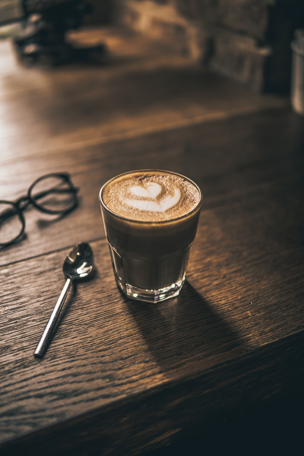 cappuccino with heart latte art on brown wooden table surface