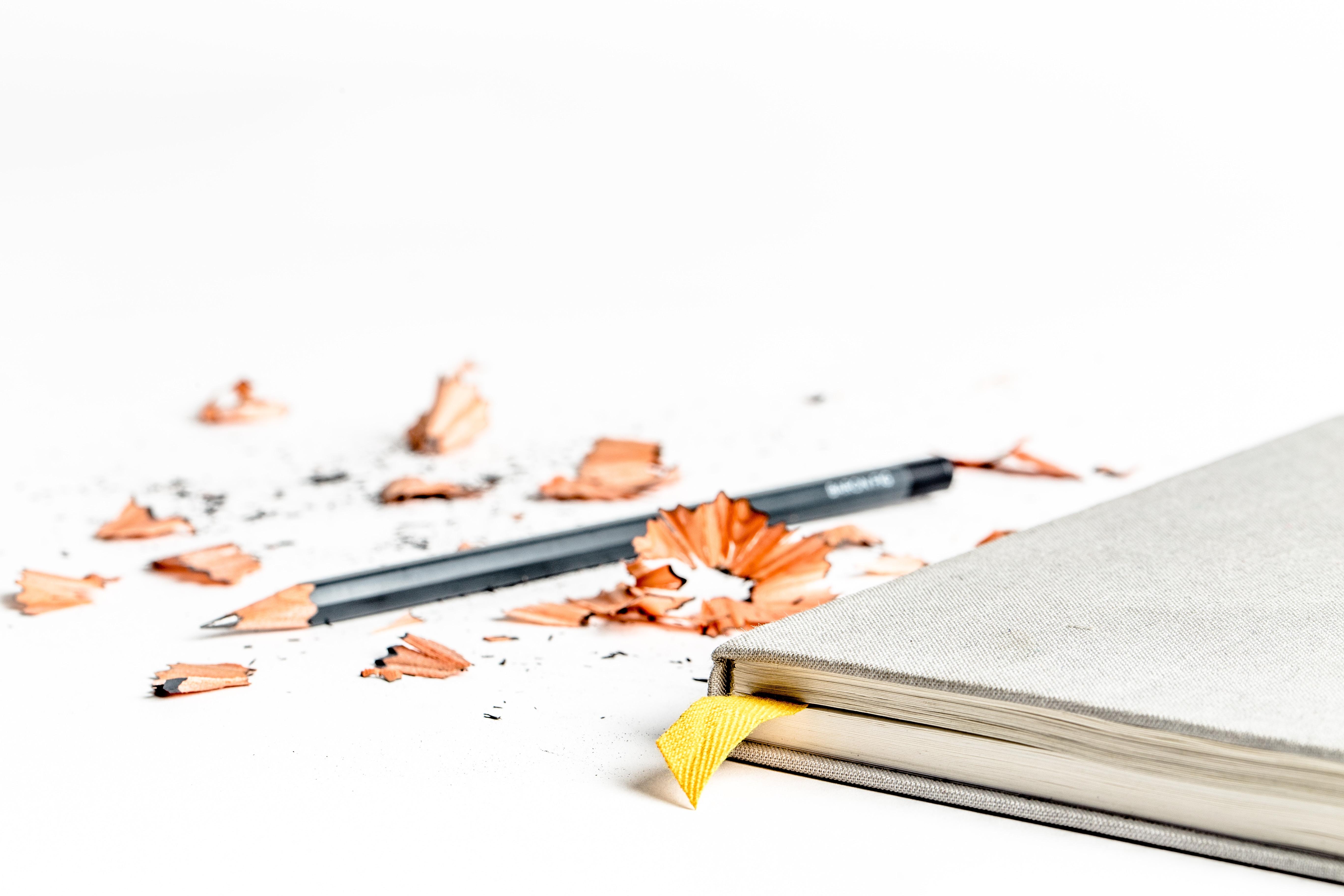 sharpened pencil near book