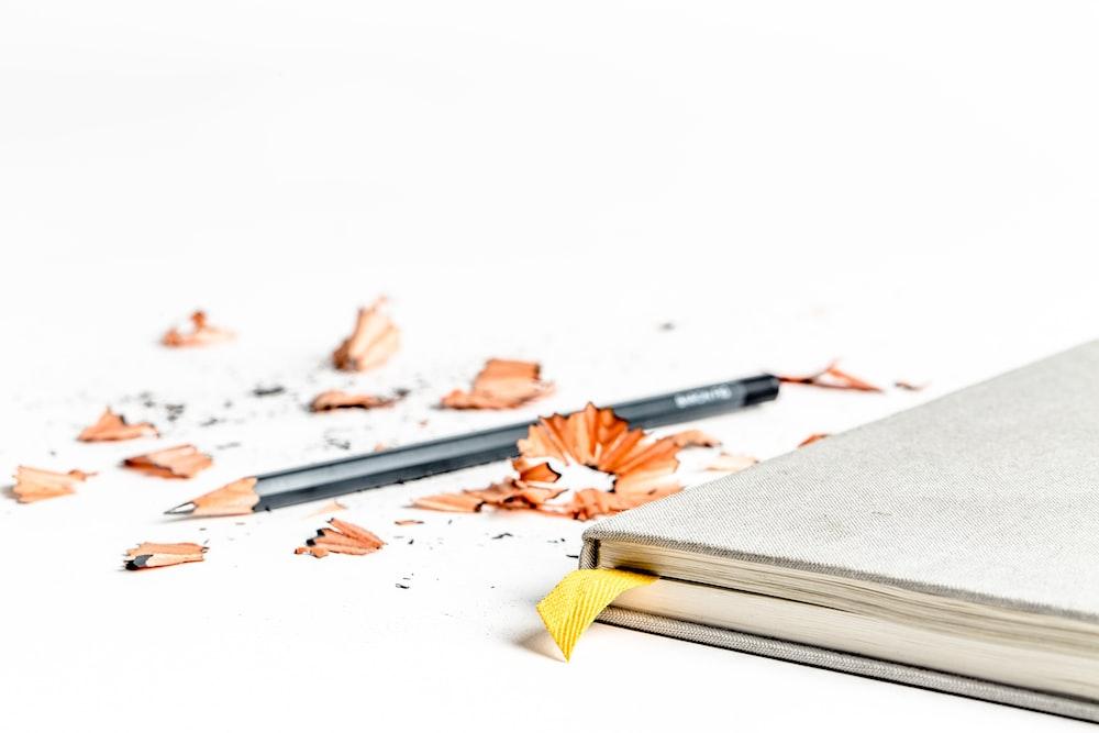 lápis afiado perto de livro