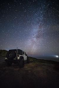 white Jeep Wrangler under starry sky