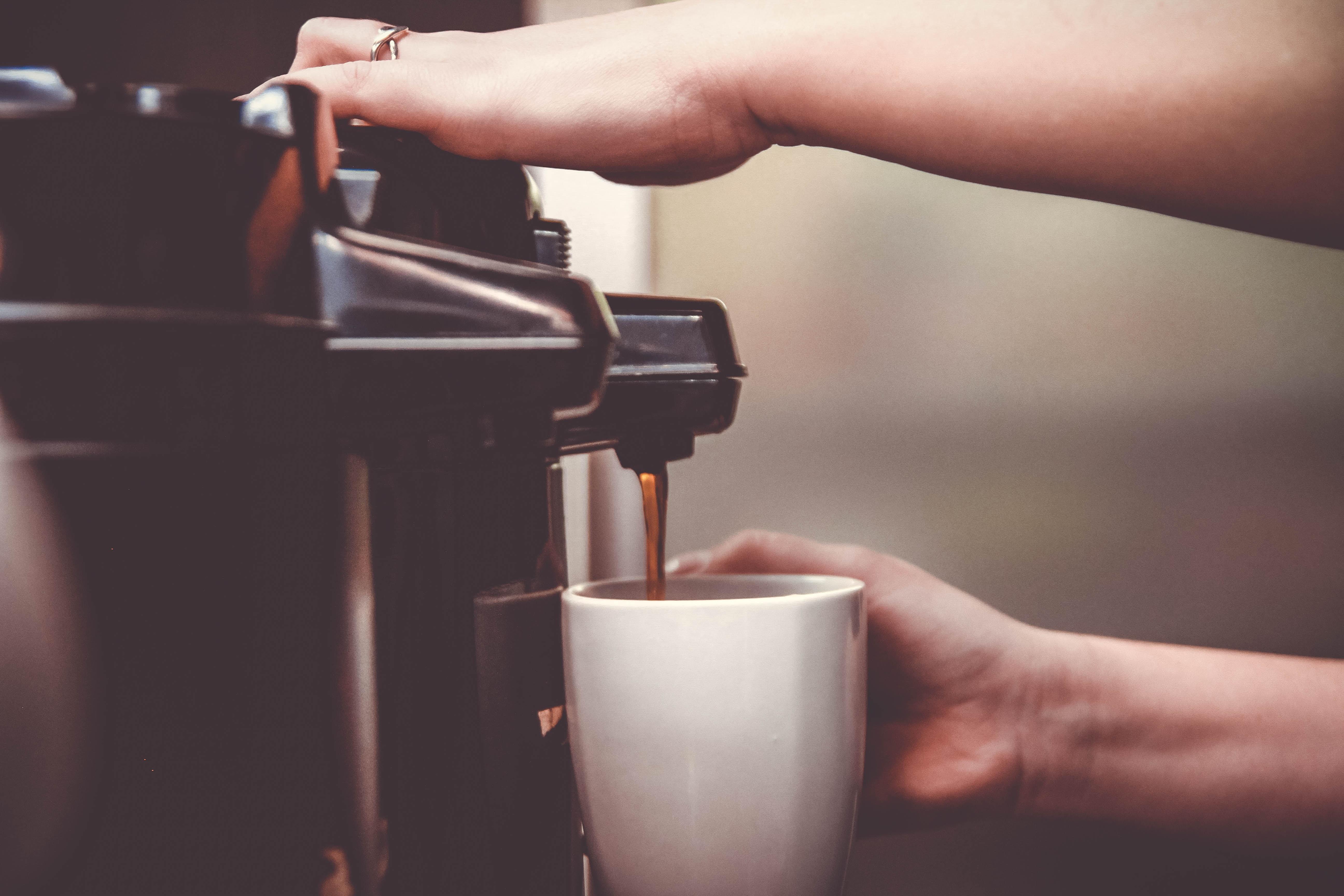 person using coffeemaker with white ceramic mug