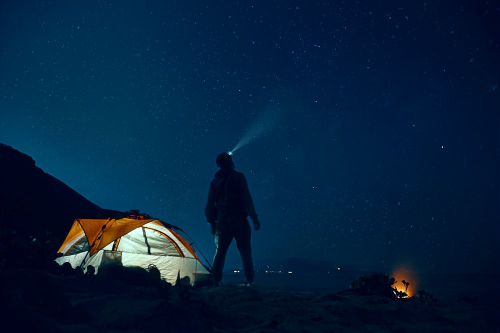 man standing beside camping tent wearing headlamp during nighttime