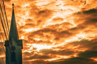 church under orange cloudy sky