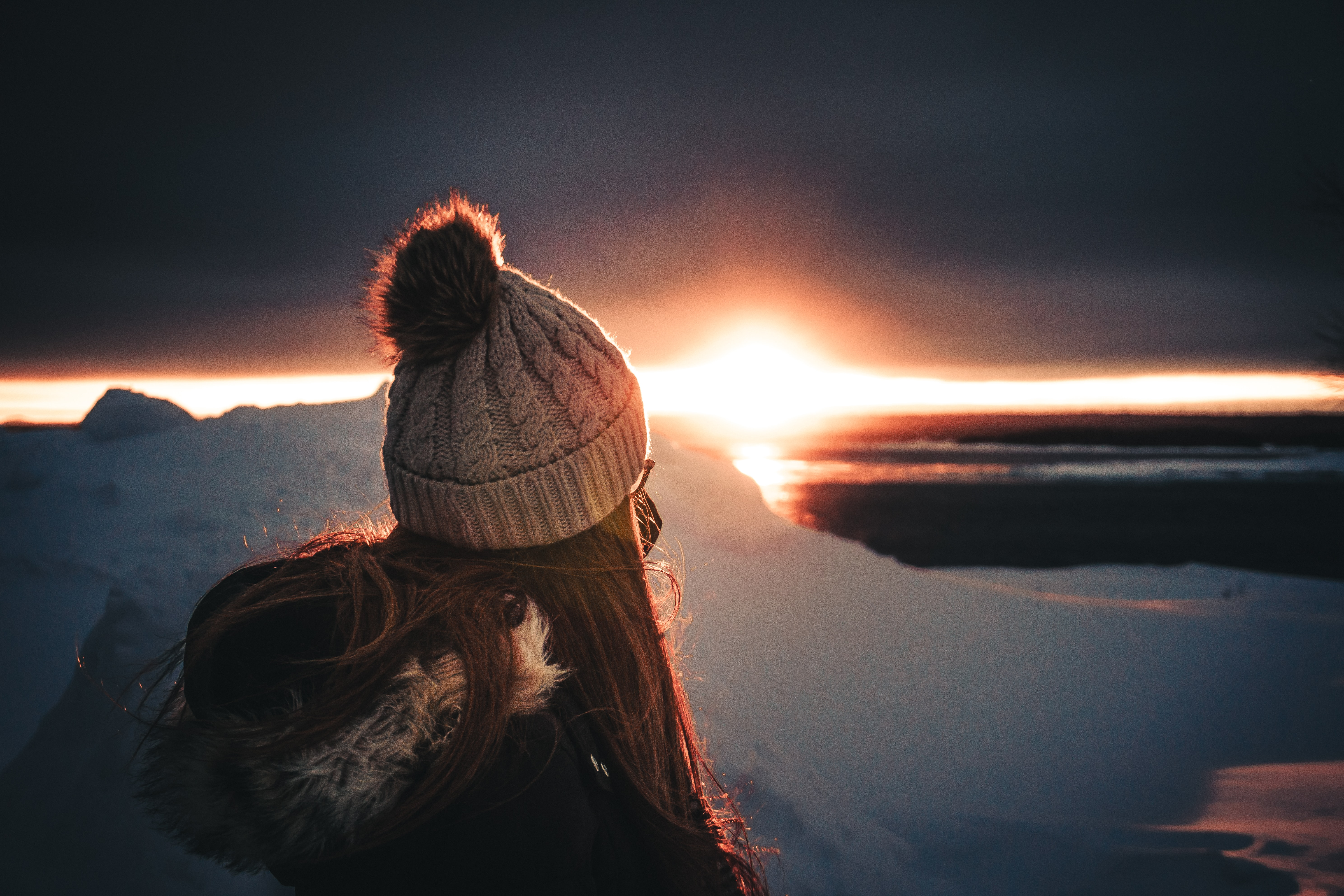 woman on top of mountain looking at sunset