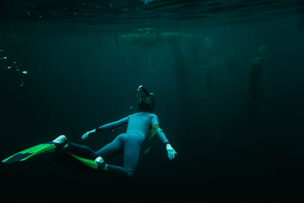 person in underwater wearing pair of flippers at daytime