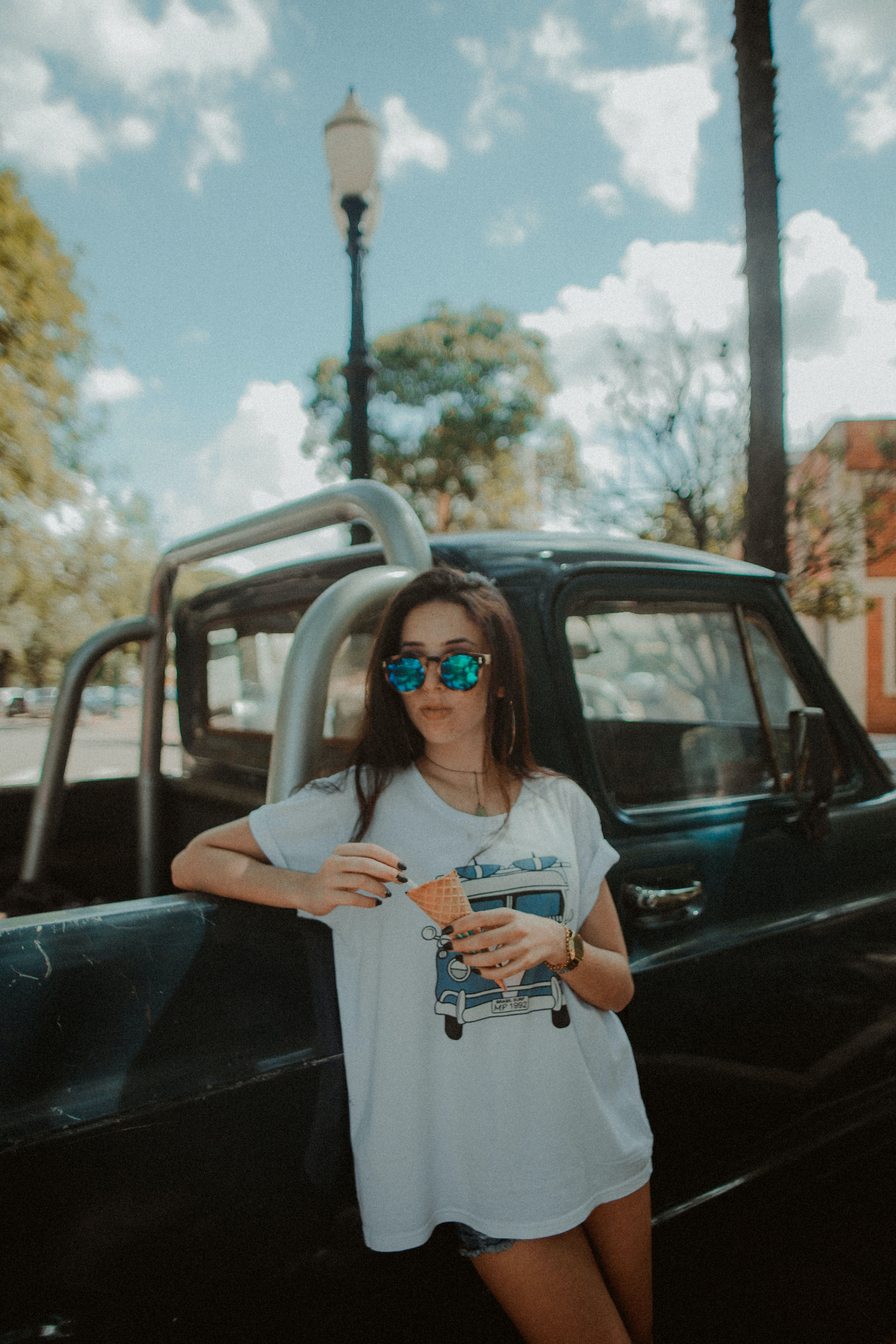 woman holding ice cream cone and leaning on pickup truck