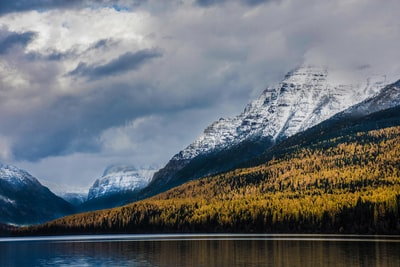 body of water near mountains glacier national park teams background