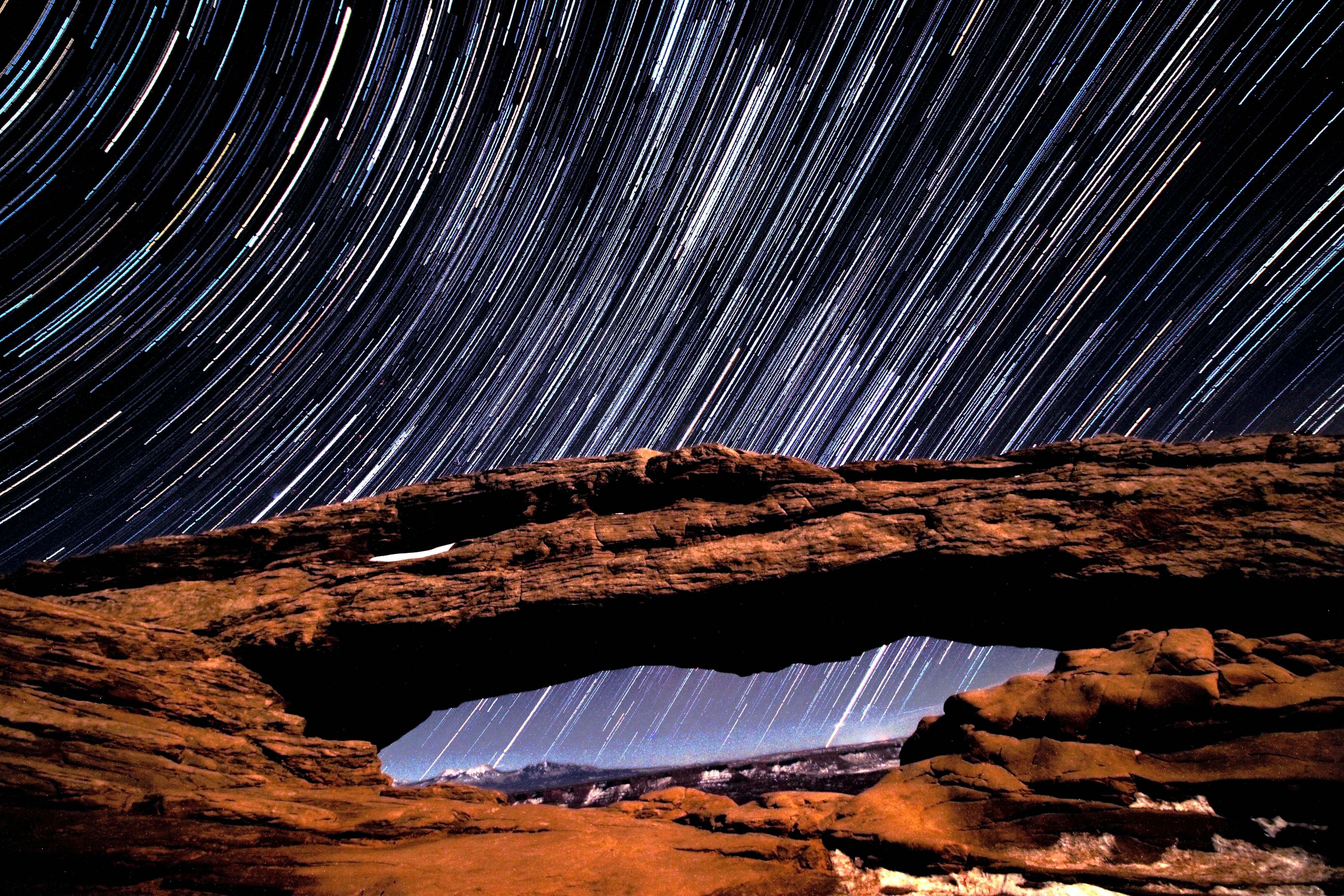 timelapse photo of stars and brown rock arch