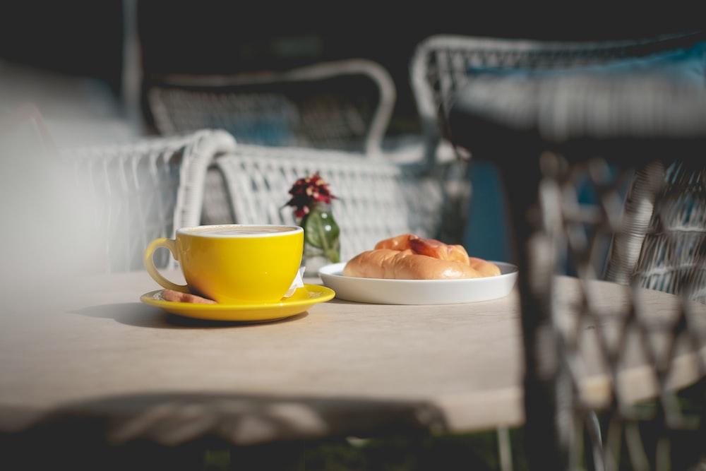 tilt-shift photography of yellow mug on table