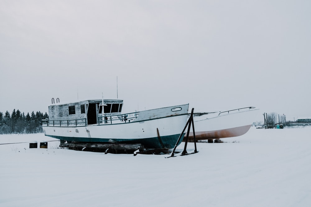 two boats on snow-covered field during daytime