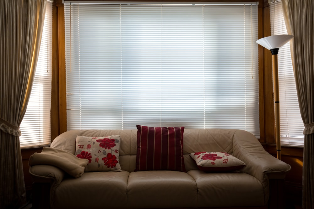 brown leather couch in front of window