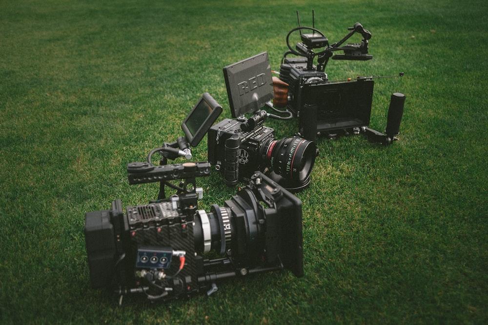 three black video cameras on green grass field