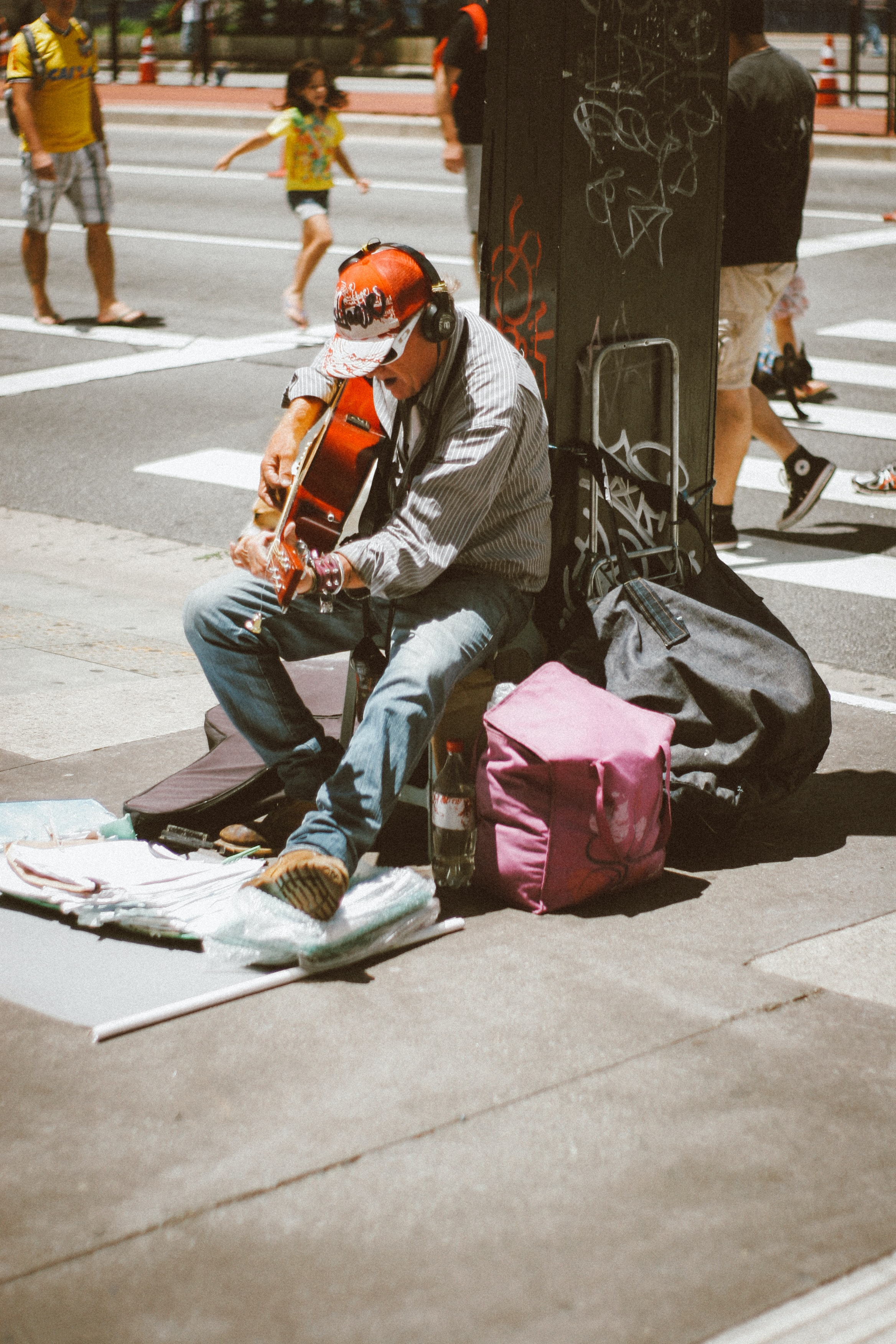 man playing guitar in front of post
