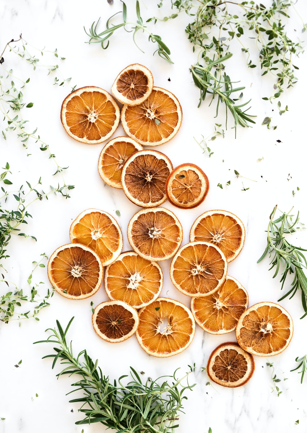 sliced lemons surrounded by green herbs