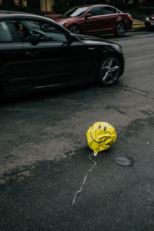 smiling emoji balloon beside black car during daytime