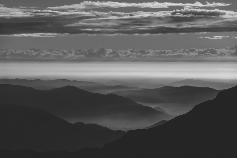 grayscale photography of clouds through mountain range