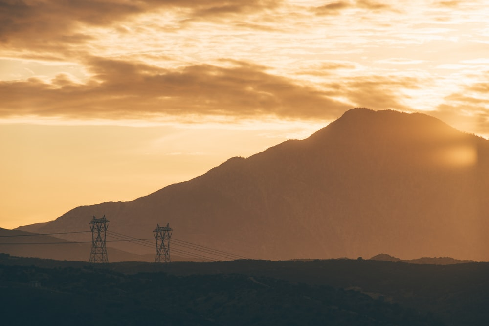sun shining over mountain and two transmission towers