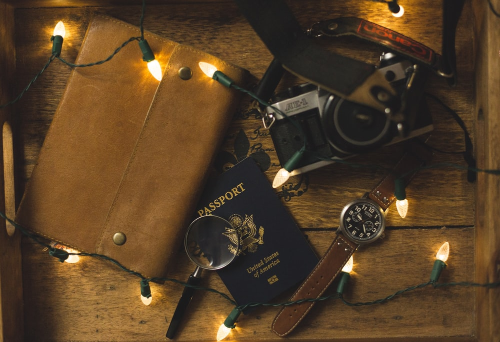 passport and SLR camera on table with string lights