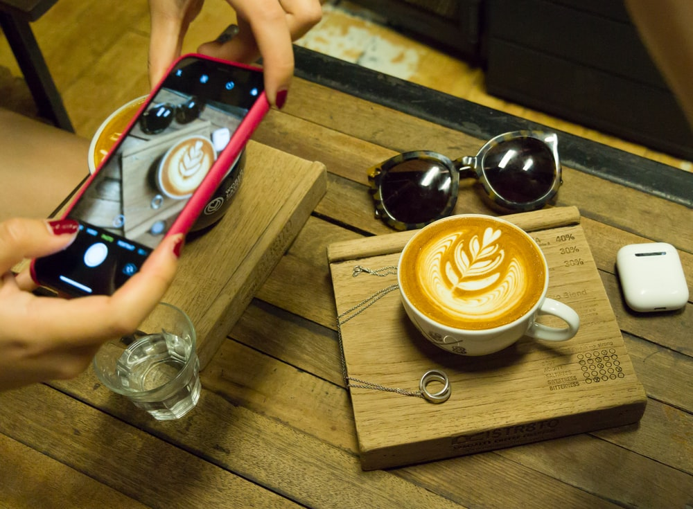 person taking photo of latte art