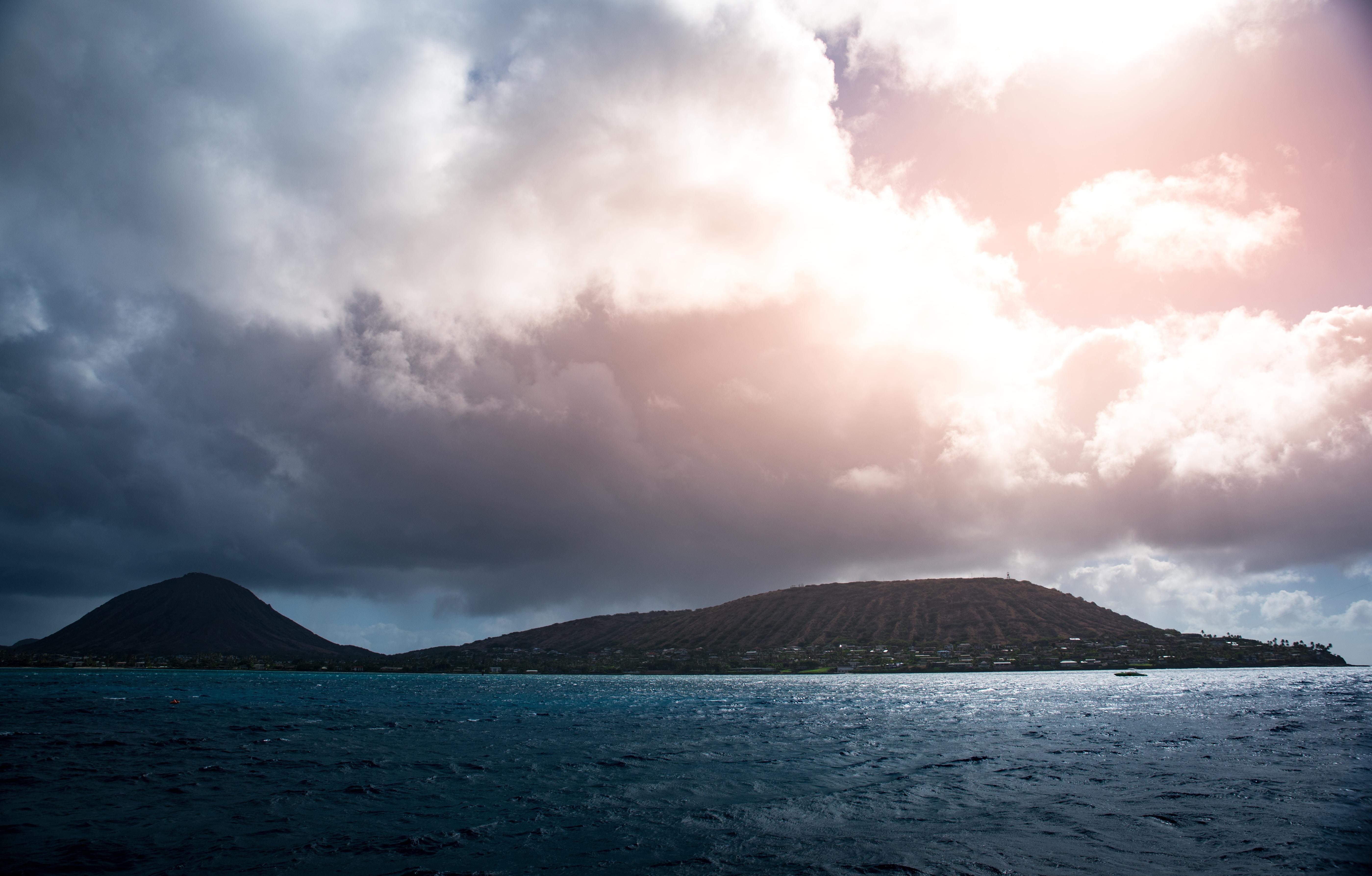 island beside body of water under cloudy sky
