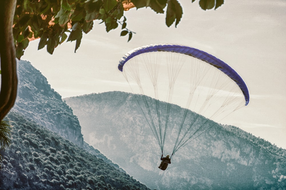 person on parachute near mountain