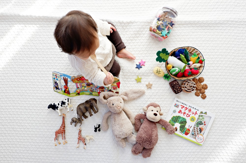 boy sitting on white cloth surrounded by toys