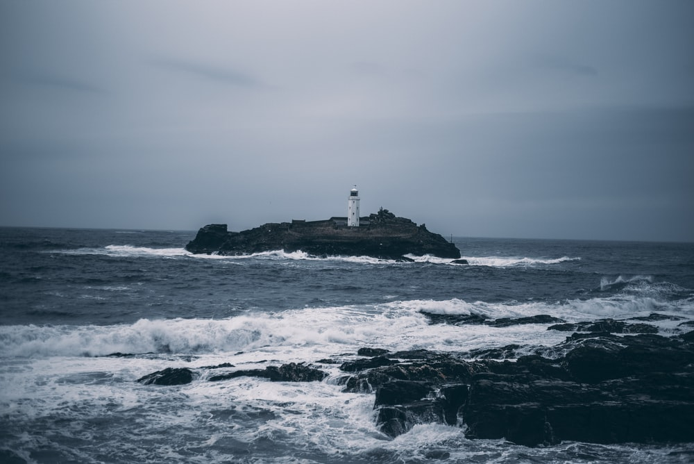 white lighthouse on rock formation surrounded by ocean