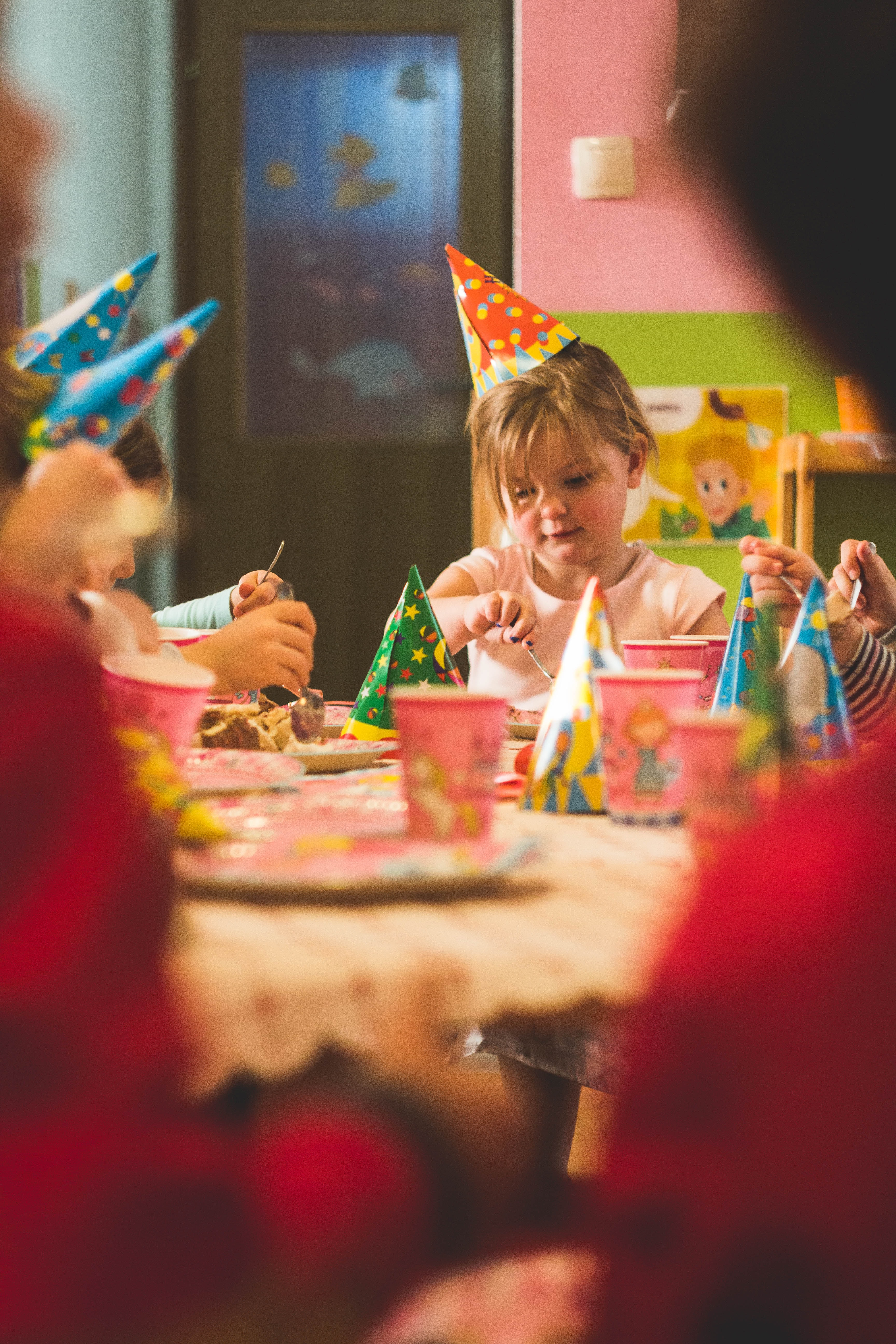 girl wearing party hat sitting in front of table