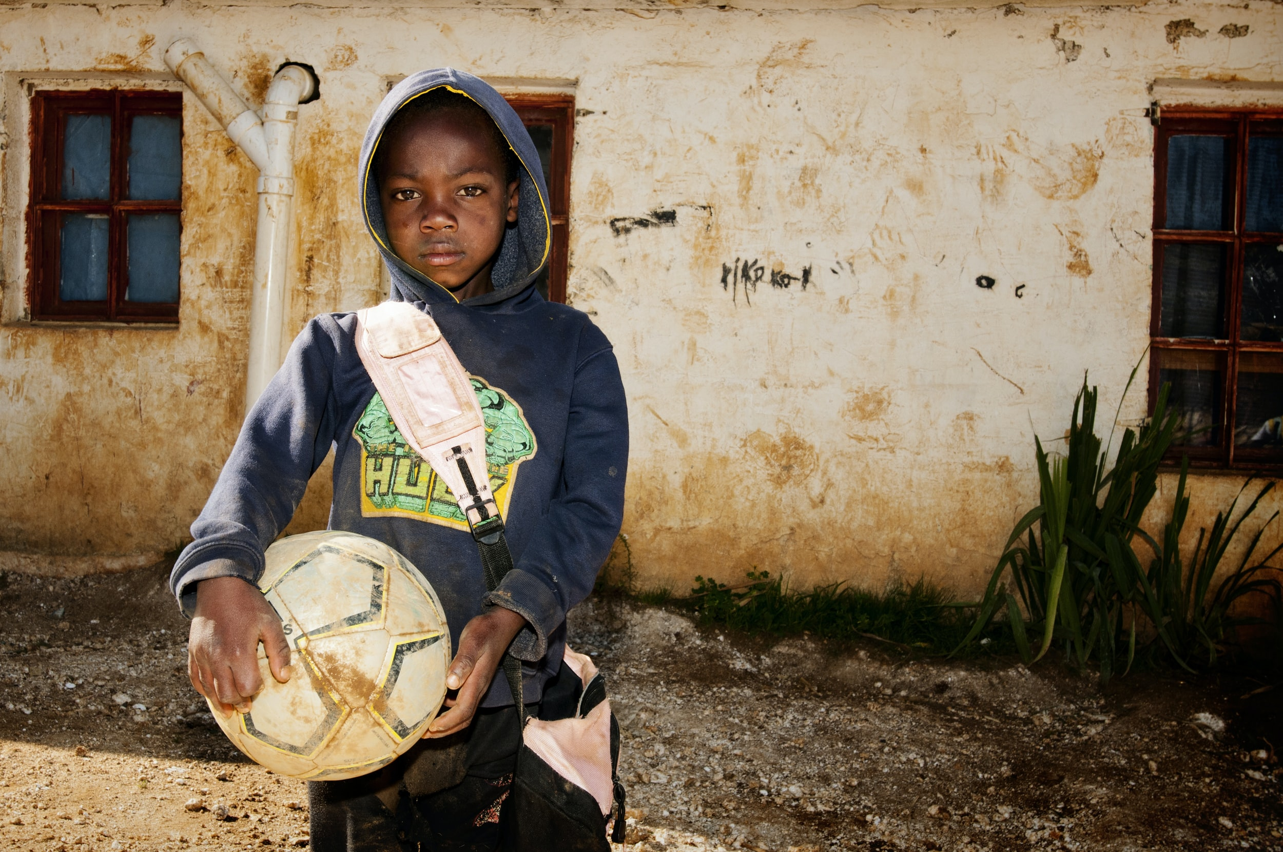 boy holding soccer ball on front of house