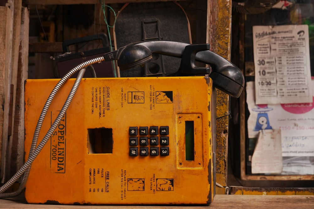 public telephone near window with papers
